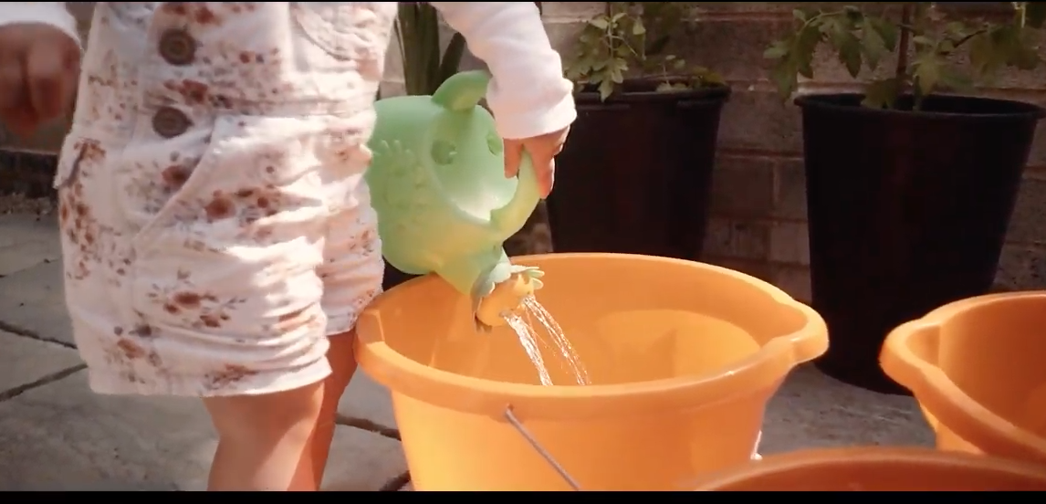 young child moving with a watering can