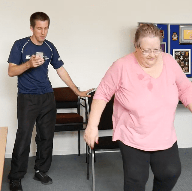 female getting up from a chair unaided.