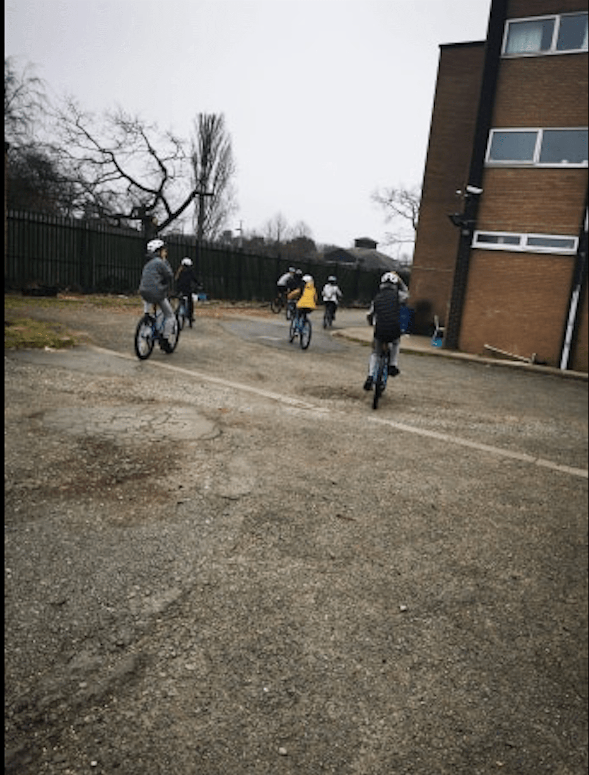4 young people on bikes riding around a housing estate
