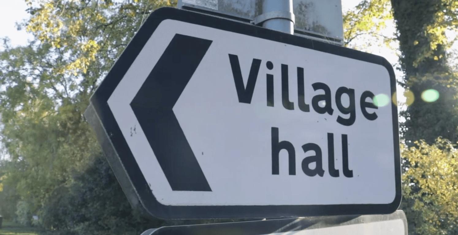 road sign saying village hall