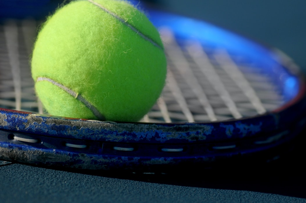 CLOSE UP OF TENNIS BALL ON RACKET