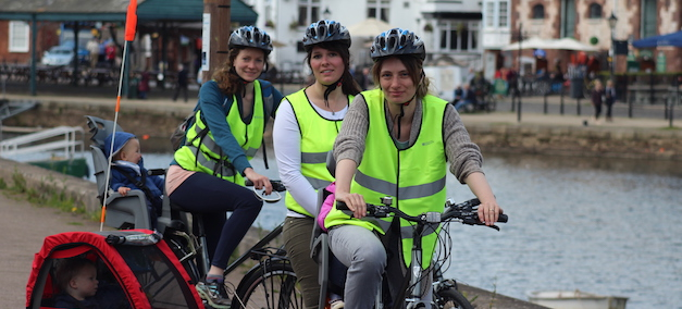 3 mums cycling with children in bike trailors