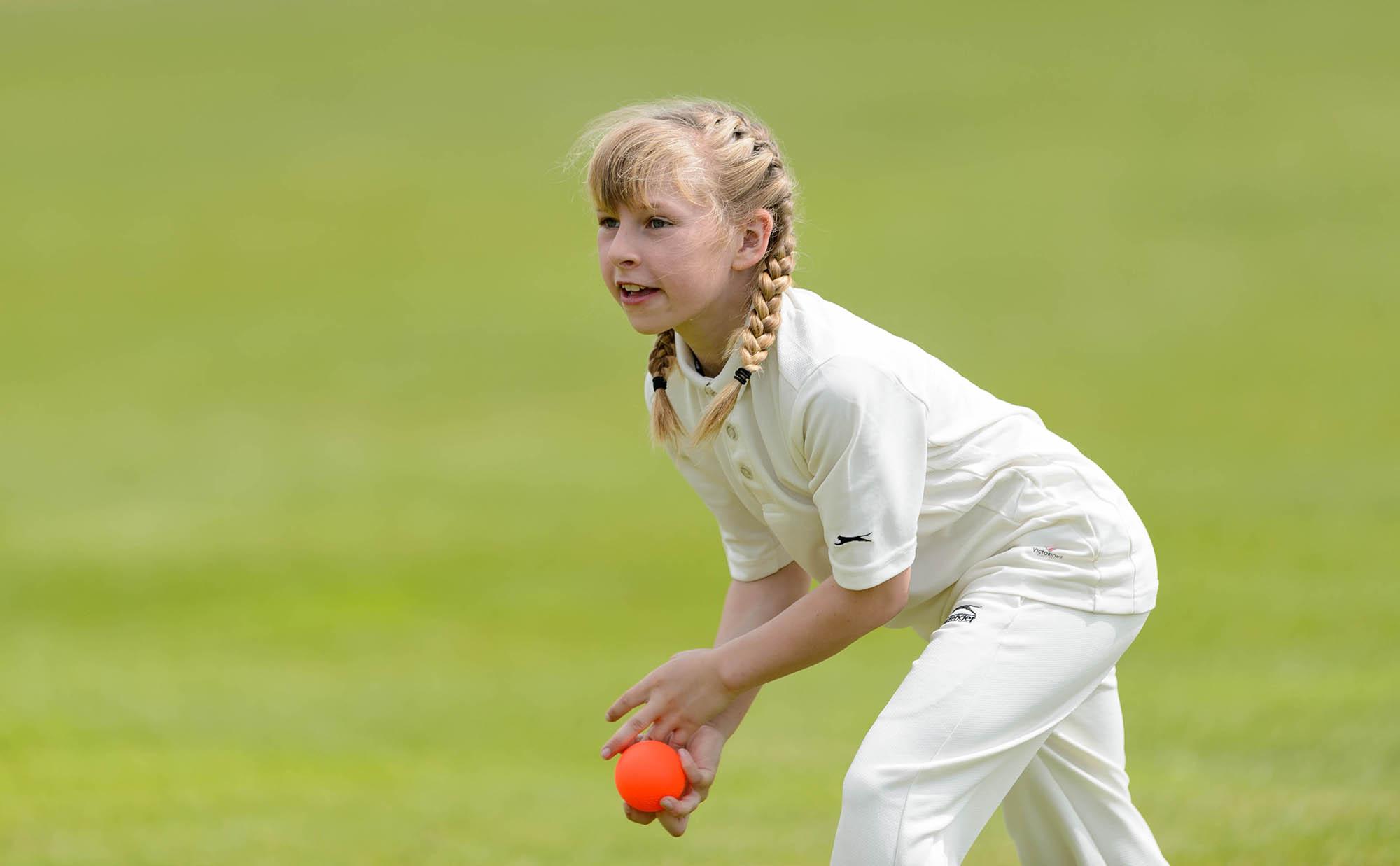young girl throwing cricket ball