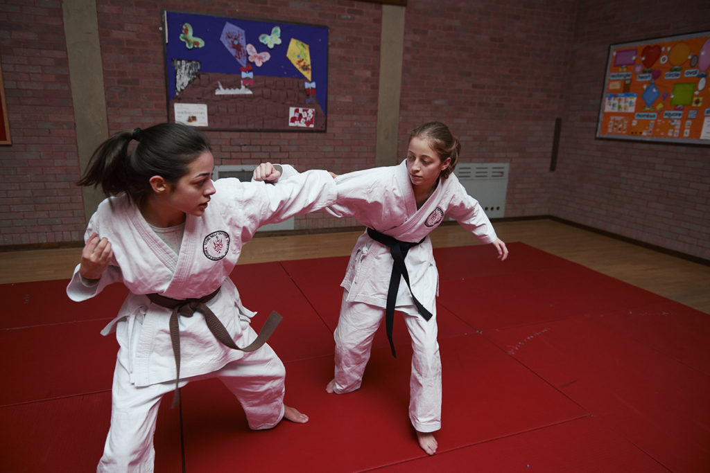 Two girls taking part in am martial arts class in a hall.
