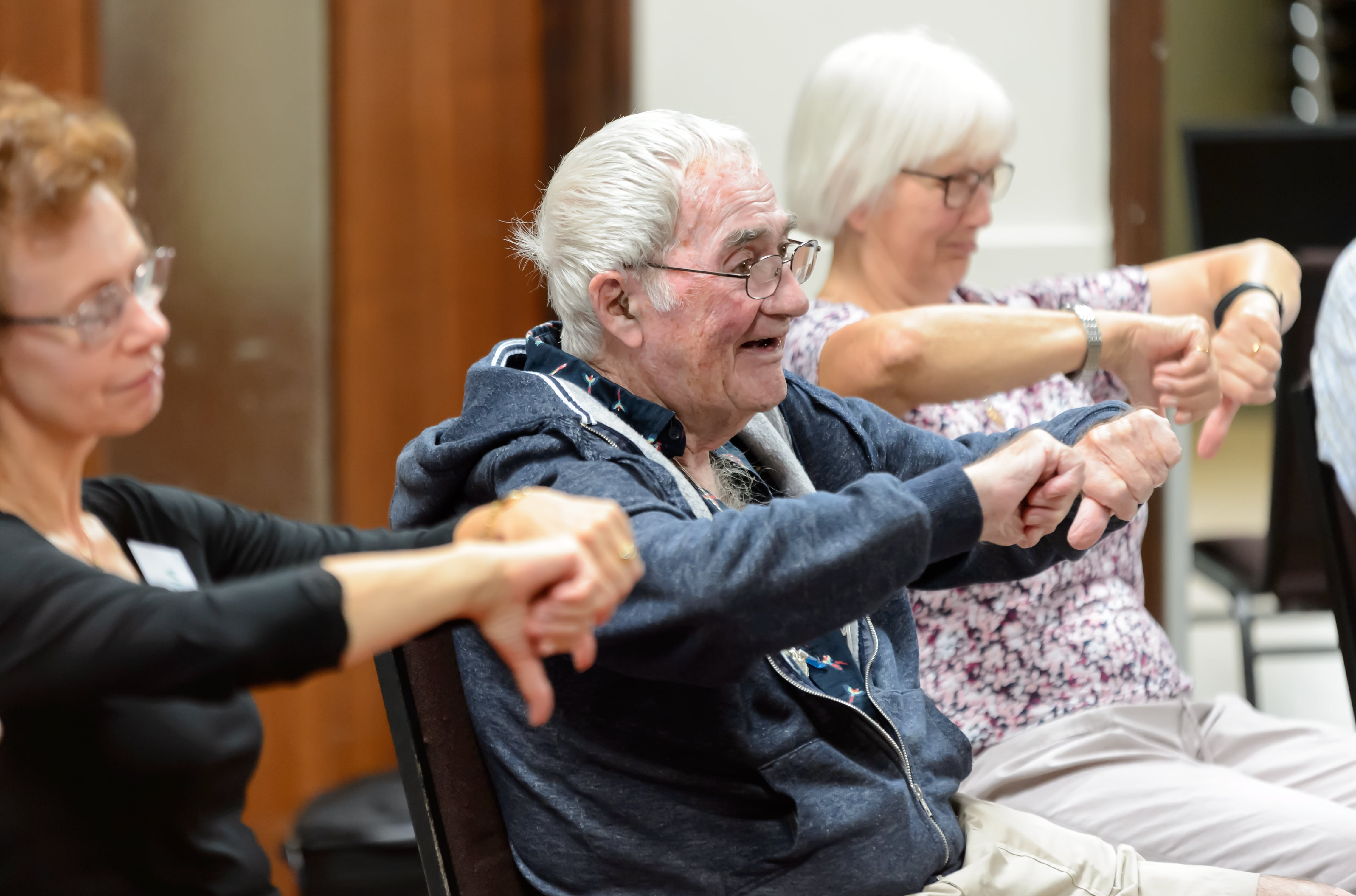 older people taking part in seated exercise class