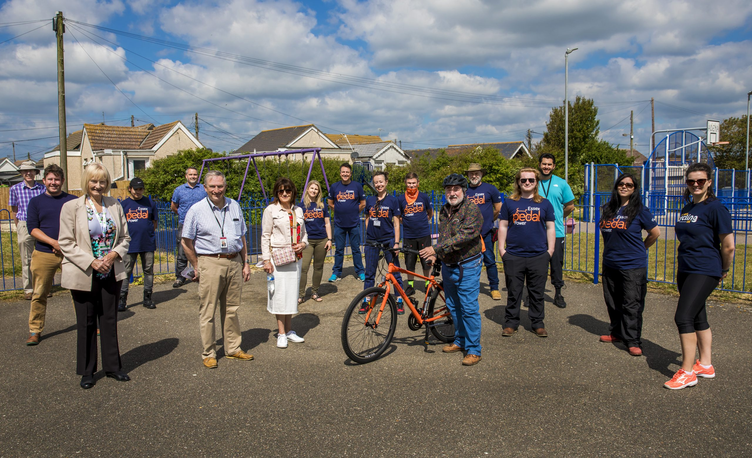 Group of people holding bikes in a park at the launch event