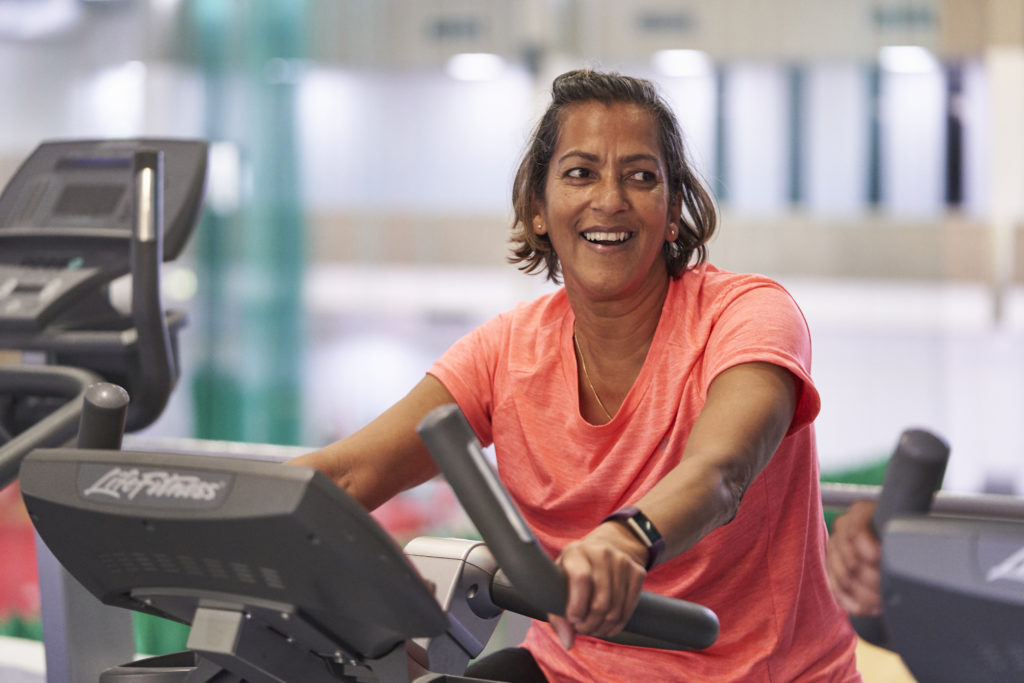 female in an orange t-shirt smiling whilst working out on a step machine in the gym