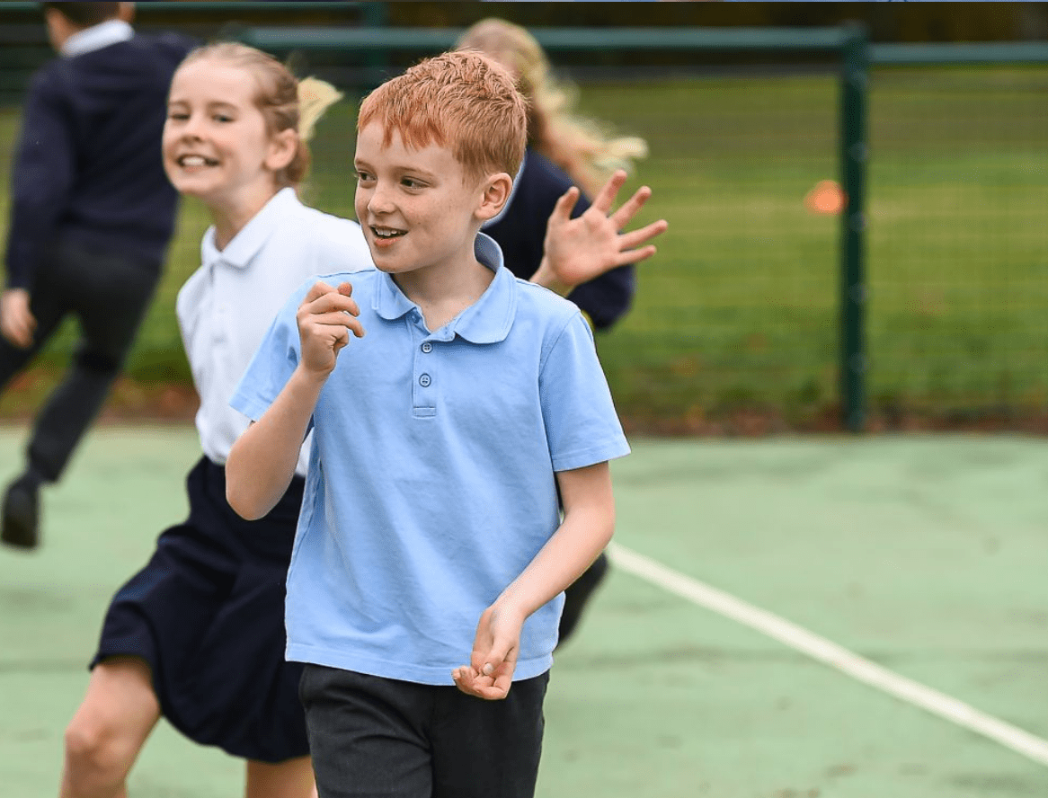 primary aged boy and girl running in a playground
