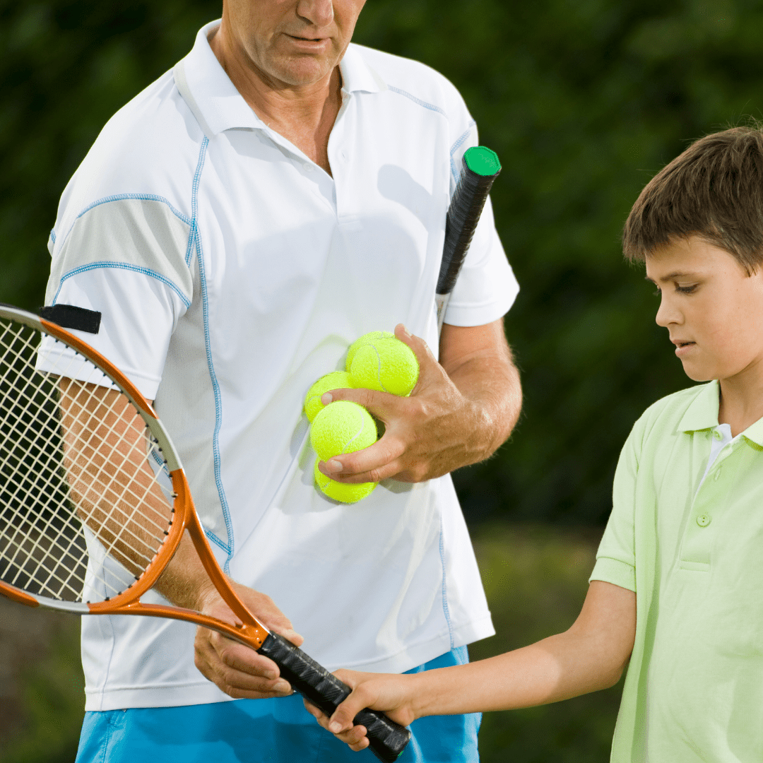 male coach showing boy how to hold a tennis racket whilst holding two tennis balls in other hand.