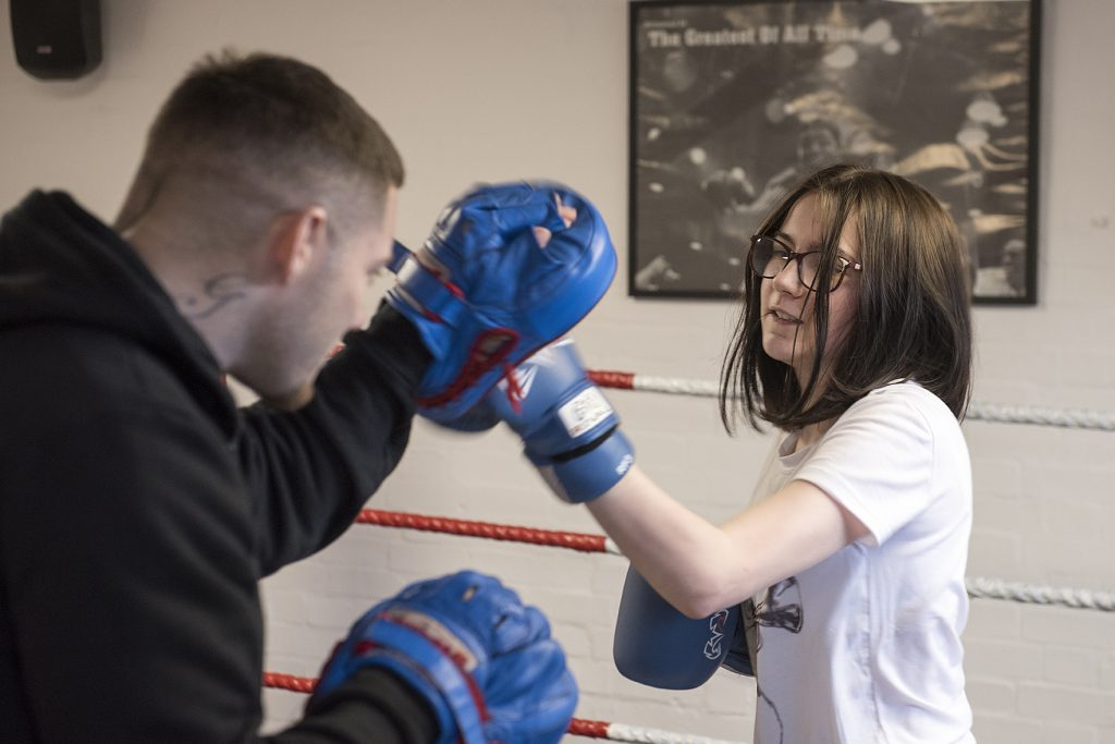 Girls boxing with an instructor