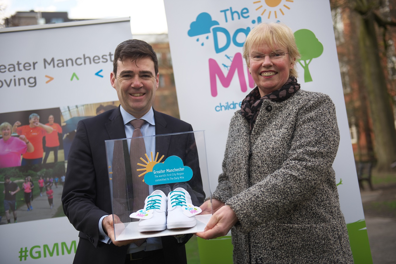 Eliane Wyllie presenting Andy Burham with special pair of 'The Daily Mile' plimsolls