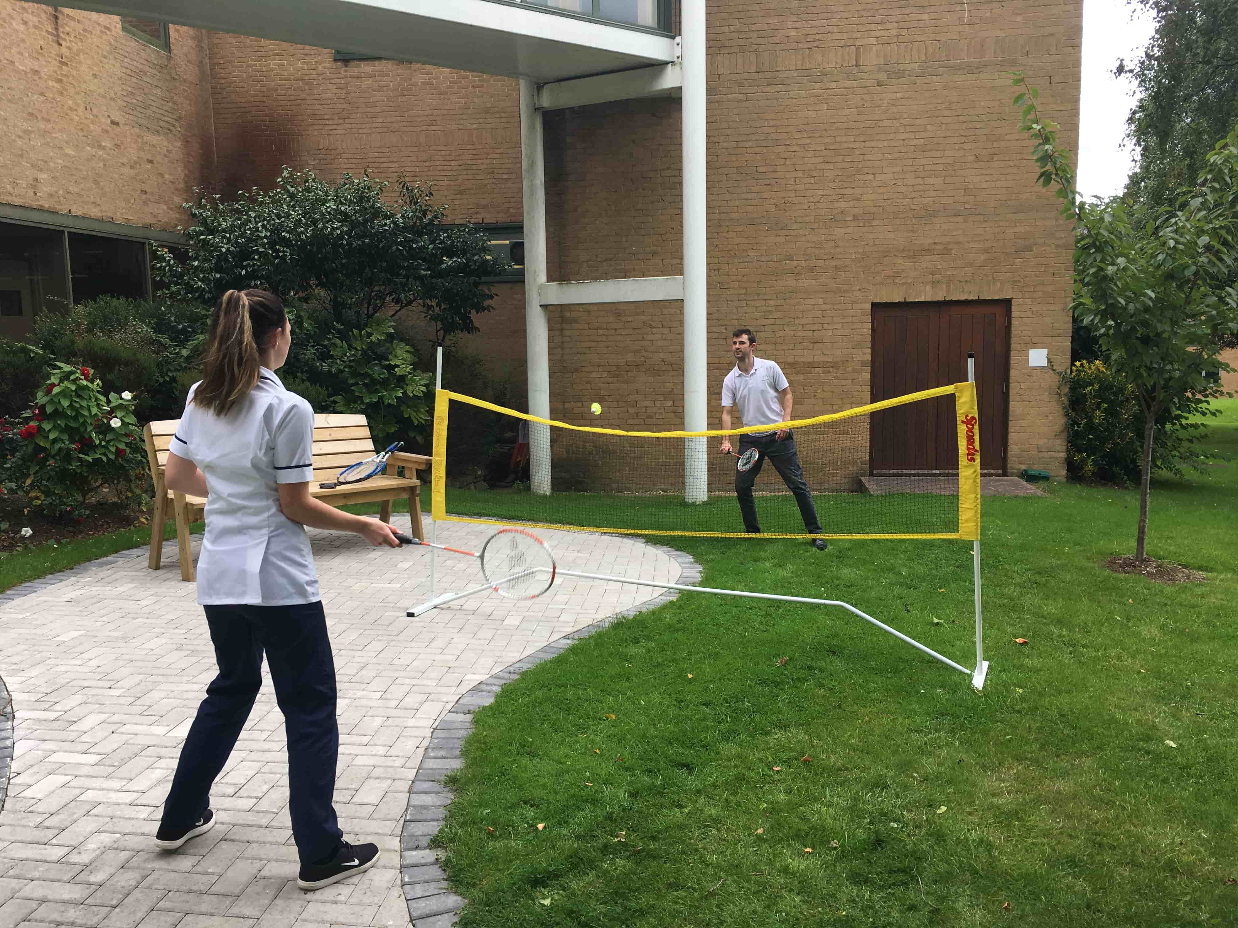 Staff playing badminton in hospital grounds
