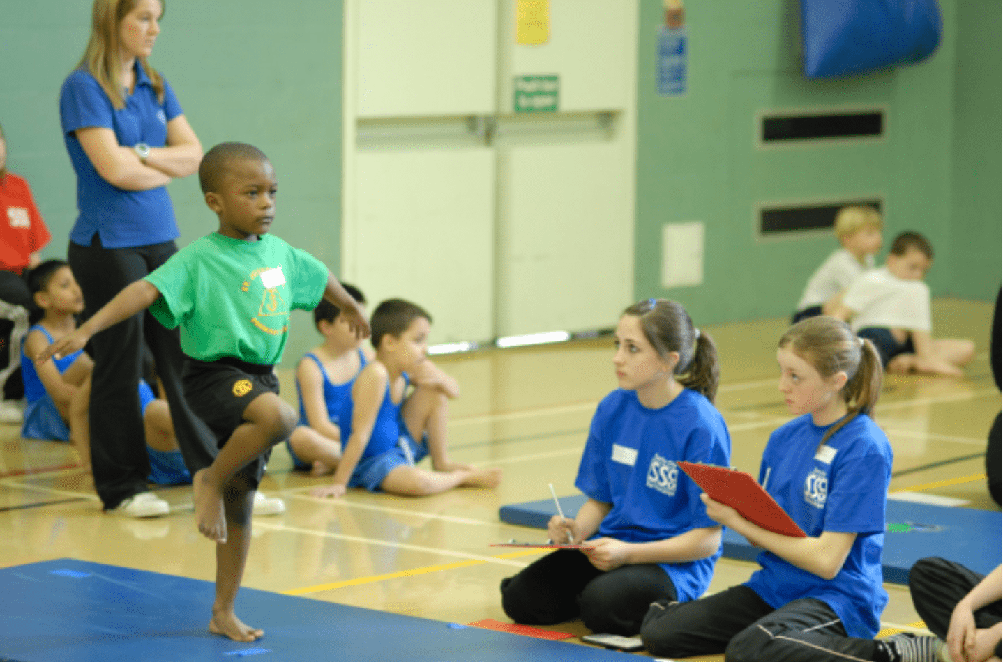 Young gymnastics being coached