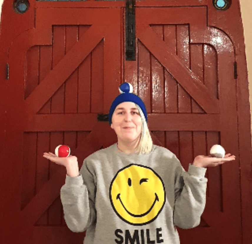 female with juggling balls against a wooden door