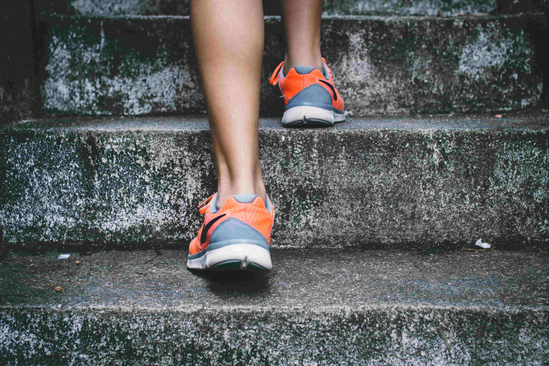 pair of feet in orange trainers walking up steps