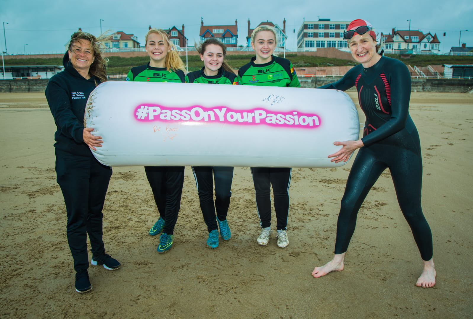 Female coaches on beach passing on inflatable batton