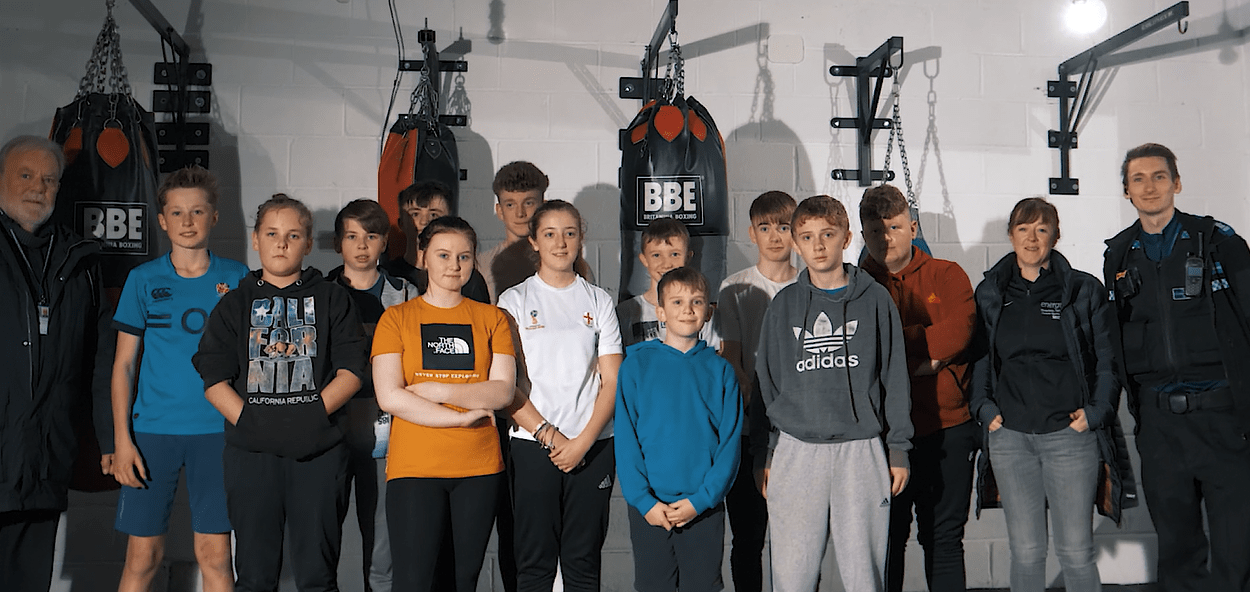group image of participants involved in boxing sessions and police officer