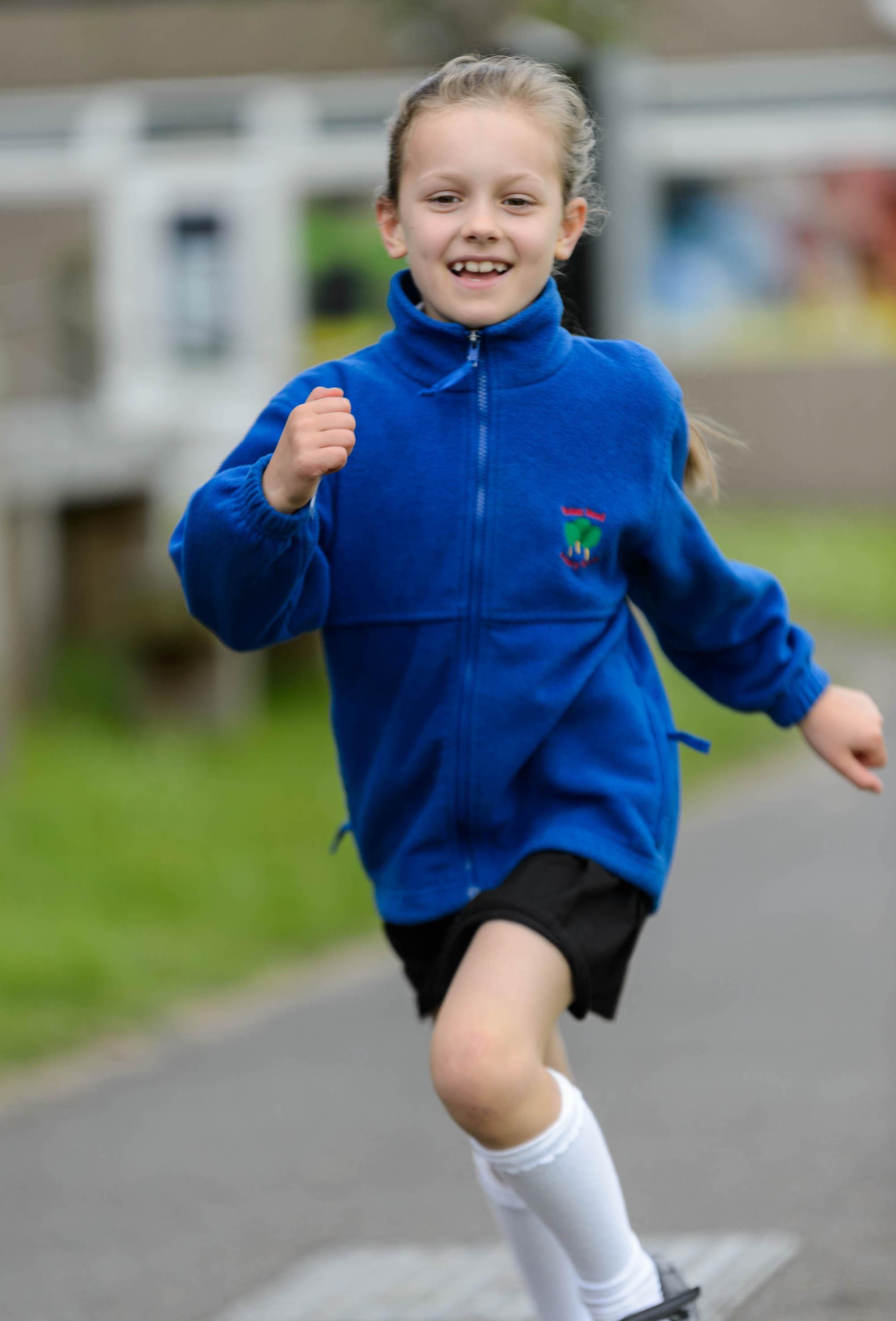 young girl running in school uniform
