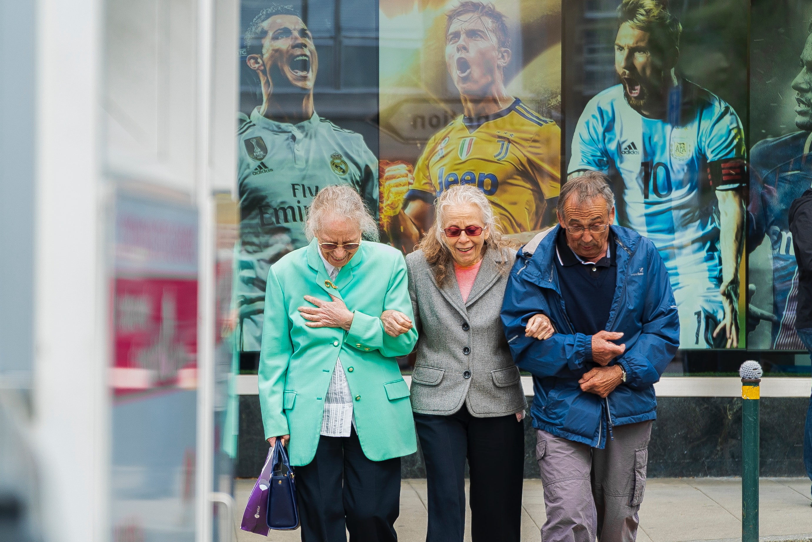 Two older females and an older man linking arms , walking and laughing past a bus stop