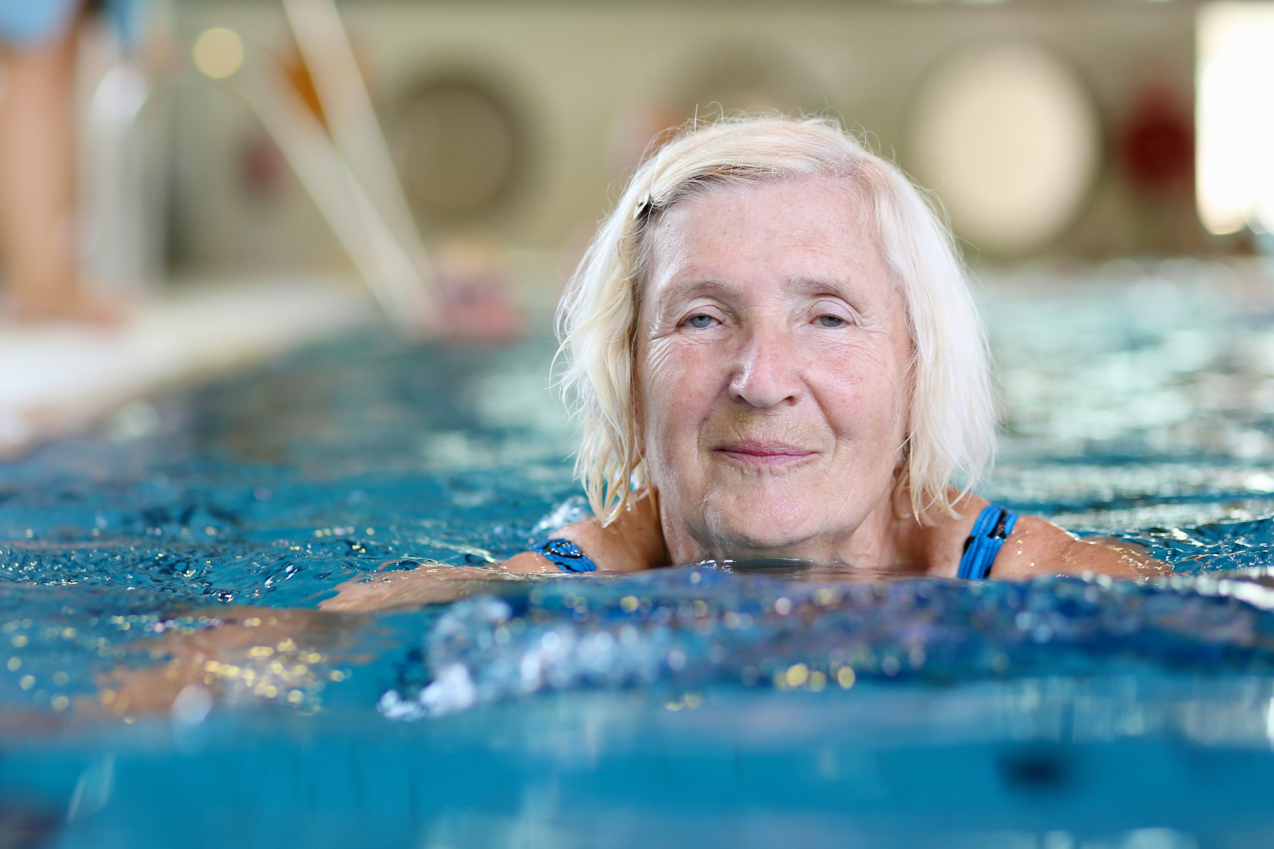older lady swimming breaststroke with her head above water