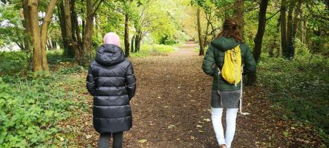Two women walking away from camera in woods in winter sunshine