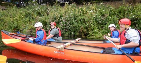 families kayaking on river