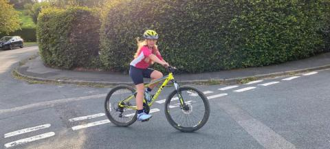 A female young carer enjoying riding her mountain bike by her house