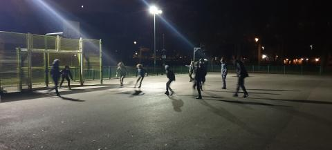 Young people playing football under floodlights