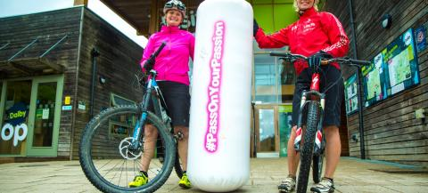 Giant baton being handed to female Mountain bike coach