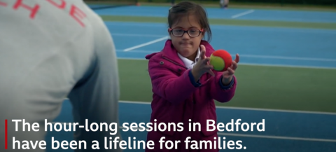 Young girl in a pink coat catching a tennis ball thrown by a coach.