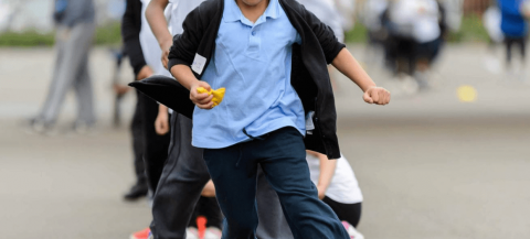 Girl running through cones in a playground, holding a beanbag, dressed in schools uniform