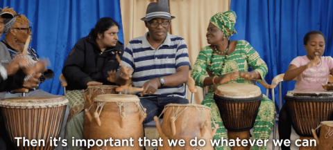 Group of  males and females from ethnic minorities taking part in a drumming session