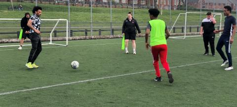 a group of young men taking part in a football session on an astro pitch in a housing estate