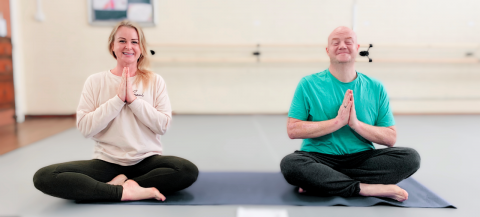 Man and women on a yoga mat in sitting yoga pose