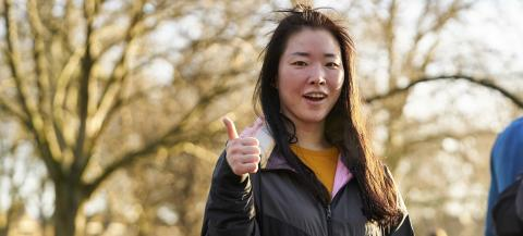 young female volunteer in a park giving a thumbs up
