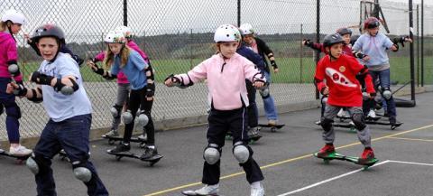 children enjoying a skateboard lesson