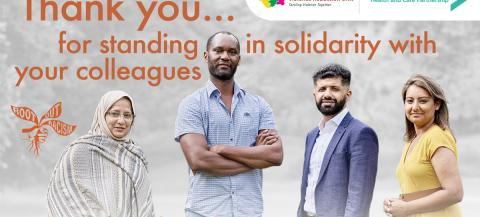 a black man, an asian man, and two asian women, one wearing a headscarf, standing in front of a poster saying thank you for standing in solitary with your colleagues.
