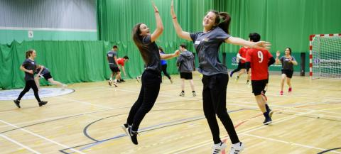 Girls giving each other a high five whilst playing handball