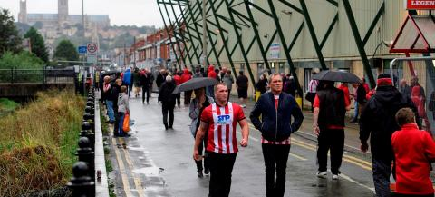 supporters walking by a football stadium