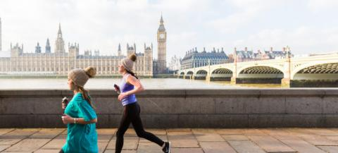 two people running along the embankment in London