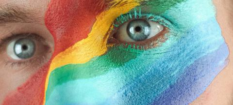 close up of a persons face with a rainbow colours painted over the bridge of the nose and right left eye