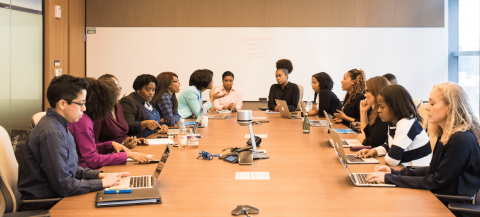 people talking around a table in a meeting room