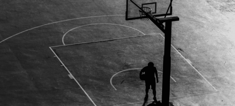 man standing with head down on a basketball court at dusk