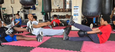 young black males doing exercises on the floor in a gym