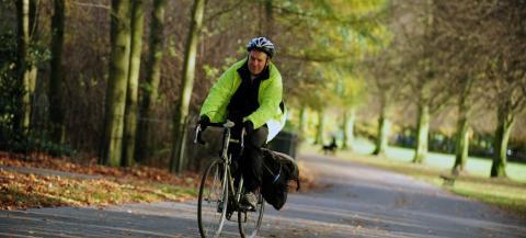 man riding bike through a park