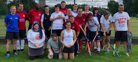 A group shot of men and women standing and kneeling on grass holding hockey sticks