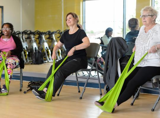 three people seating using resistance bands to exercise