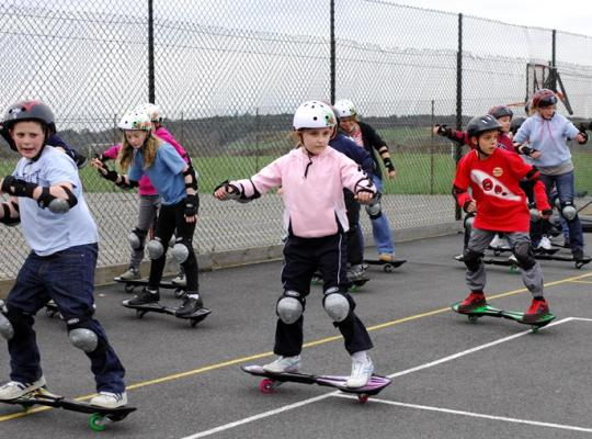 children enjoying a skateboard lesson