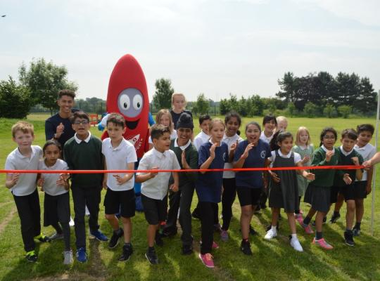 Group of school children and Mascot Zoom cutting ribbon at the launch