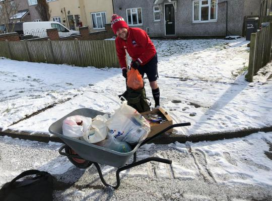 Geoff collecting food parcels in a wheelbarrow in the snow